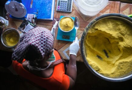 Person measuring bowl of nutritional yeast