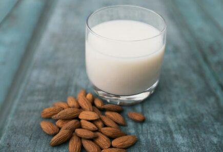 Glass of milk next to almonds