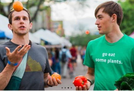 Two people holding fruits and vegetables talking