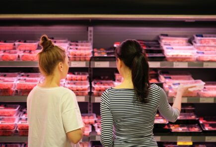 People shopping in meat aisle of supermarket