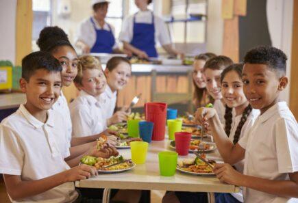 Kids eating at table smiling at camera