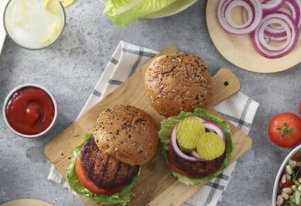 Plant-based burgers on cutting board with chips and condiments