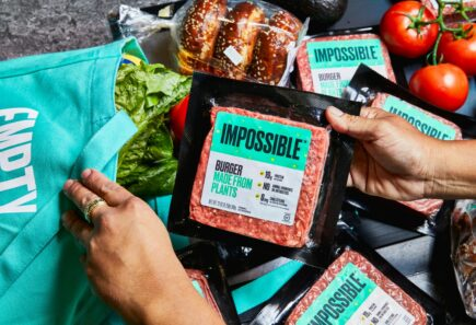 Person putting Impossible meat into grocery bag
