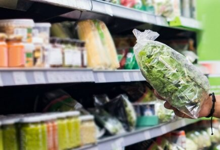 Person holding back of spinach in supermarket