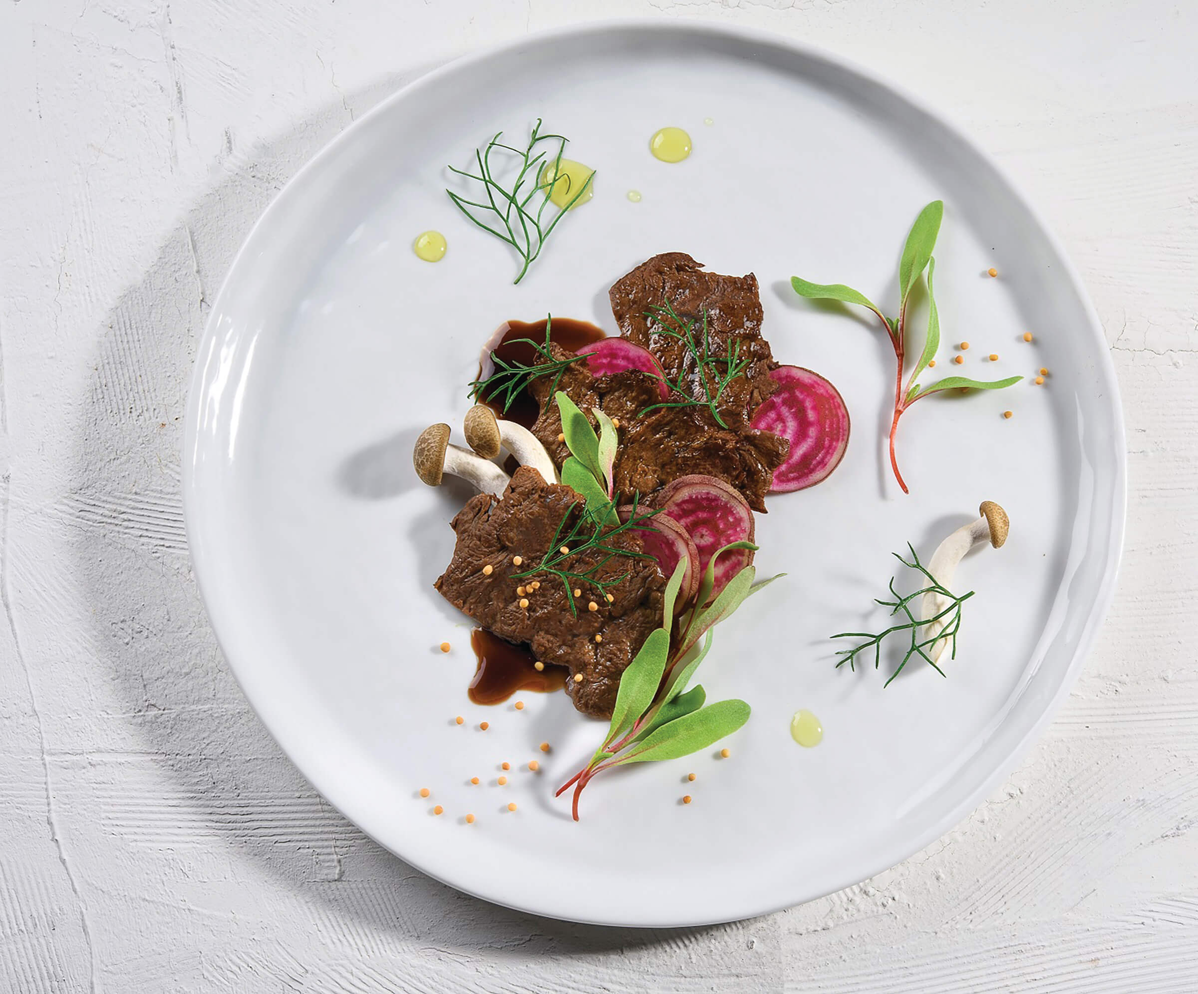 Cultivated meat plated on a white dish