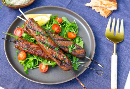 A plate piled with grilled Beyond Meat plant-based Mediterranean Skewers on a bed of greens and grape tomatoes