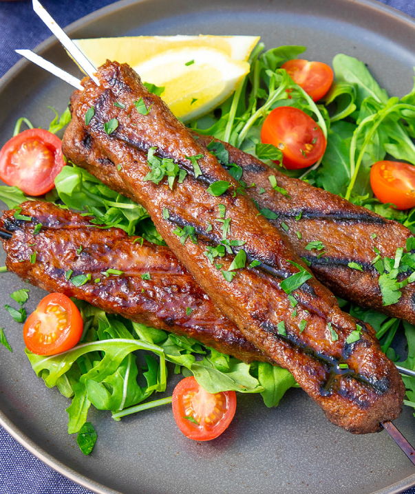 A plate piled with grilled beyond meat plant-based meditteranean skewers on a bed of greens and grape tomatoes