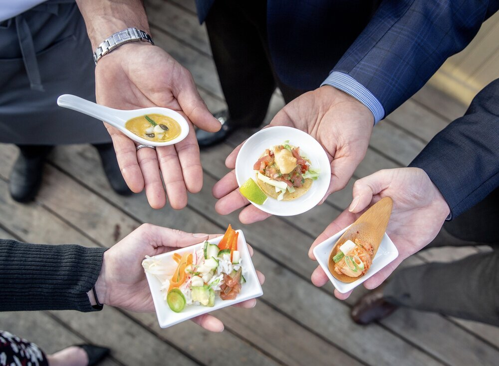 A close up on the hands of four people in business attire holding BlueNalu cultivated seafood-based appetizers on small plates