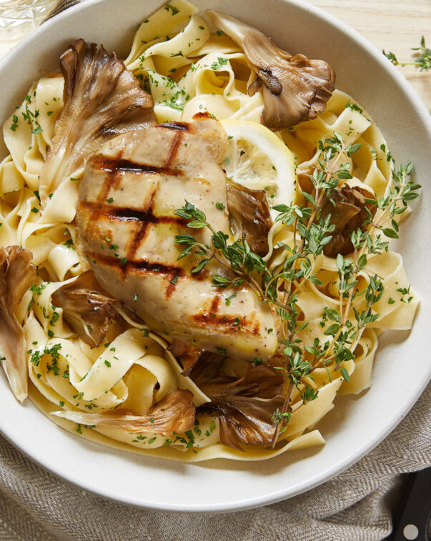 Cultivated grilled chicken on a bed of mushroom pasta and herbs viewed from above