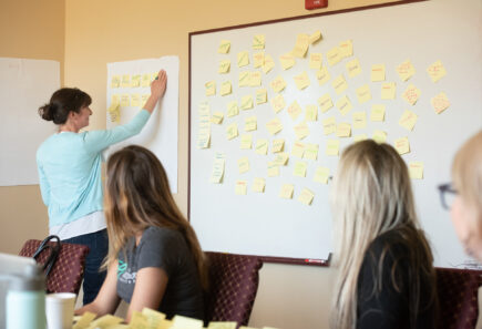 Three GFI teammates brainstorming ideas using post-it notes
