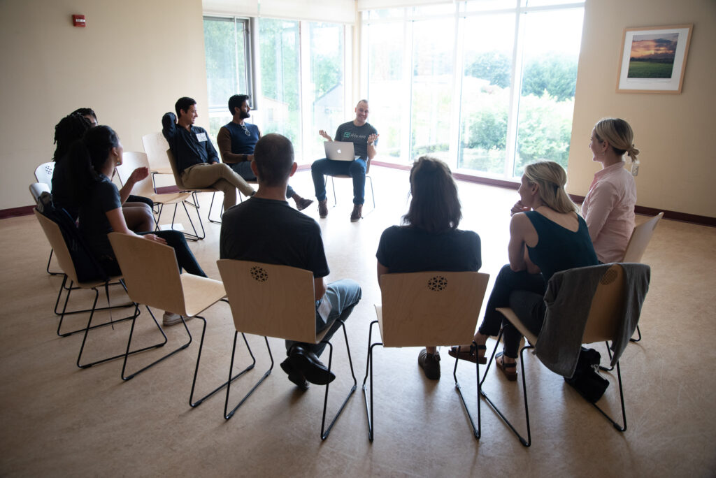 A group of GFI staff seated in a circle of chairs, mid-discussion