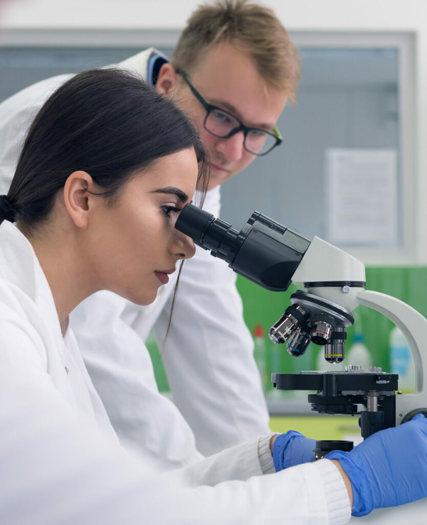 Lab partners looking in microscope