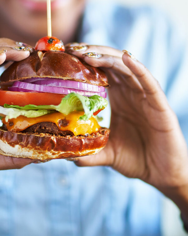 Close up view of a woman holding a delicious plant-based burger in her hands