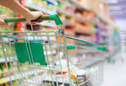 Close up of a grocery cart being pushed down an aisle