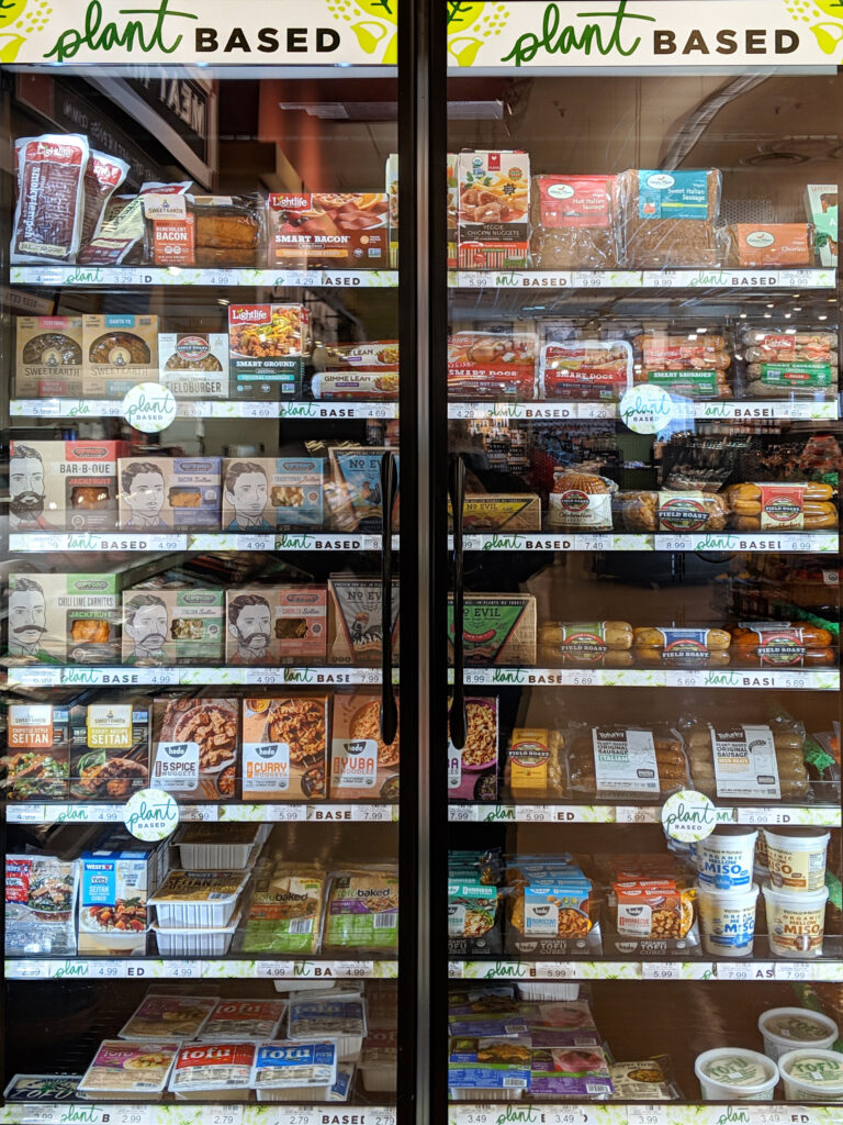 Door signage and shelf tags demarcate plant-based foods in the heinen's refrigerated section.