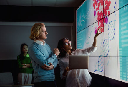 Scientists looking at a screen displaying animal cells and a DNA double helix