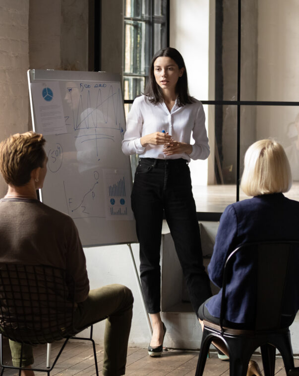 Confident woman presenting to a group of investors in an office conference room