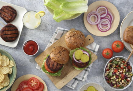 Burgers with toppings, chips, and bean salad