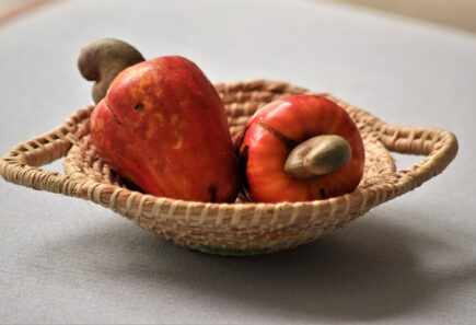 Cashew apples sitting in a basket