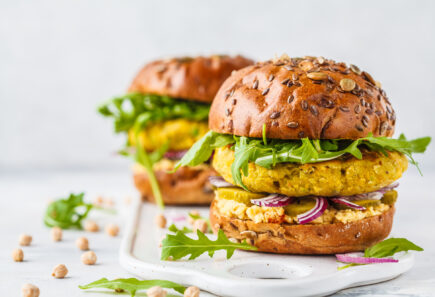Plant-based burgers topped with arugula on a white stone counter
