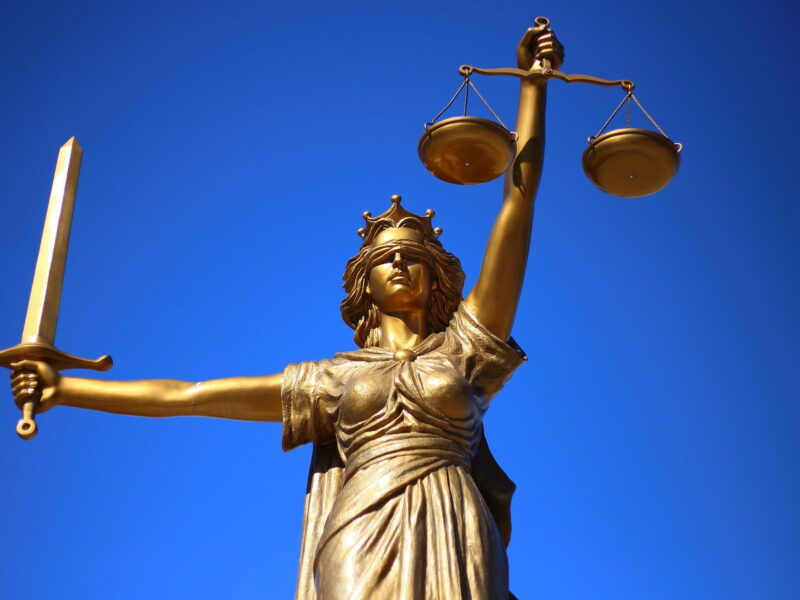 Bronze scales of justice with blue background