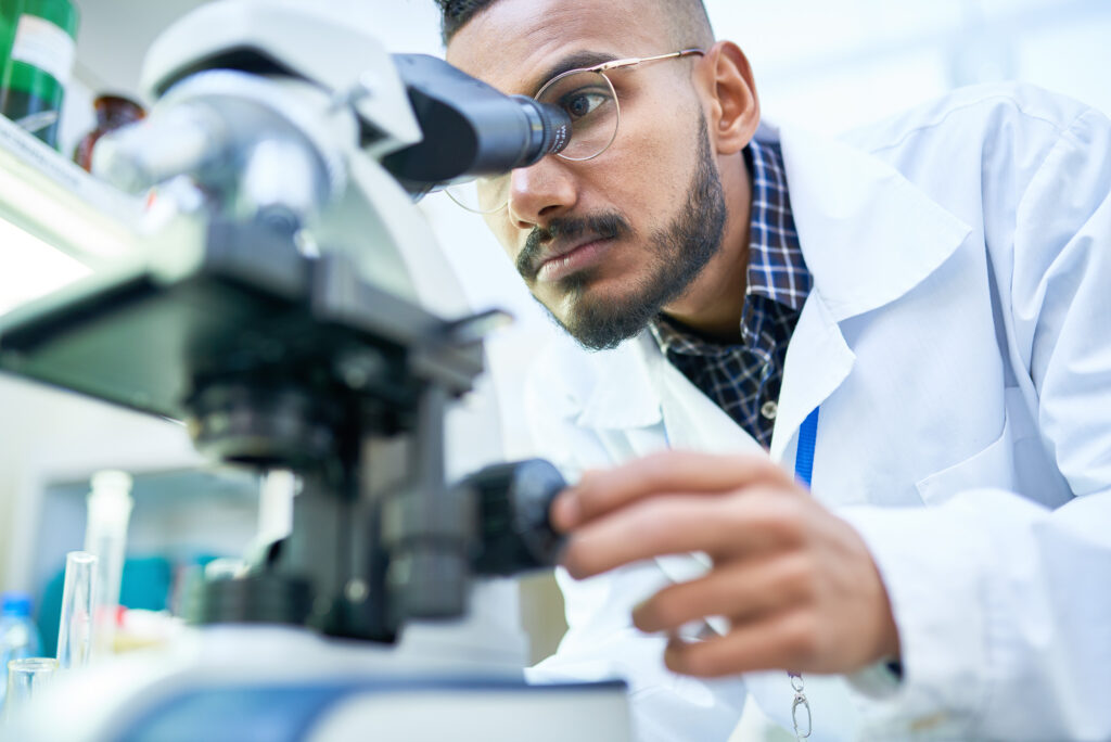A scientist looking into a microscope