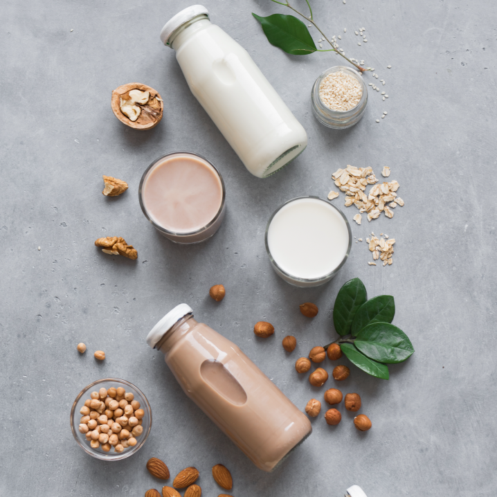 Plant based milk bottles and ingredients artistically arranged on a gray stone background