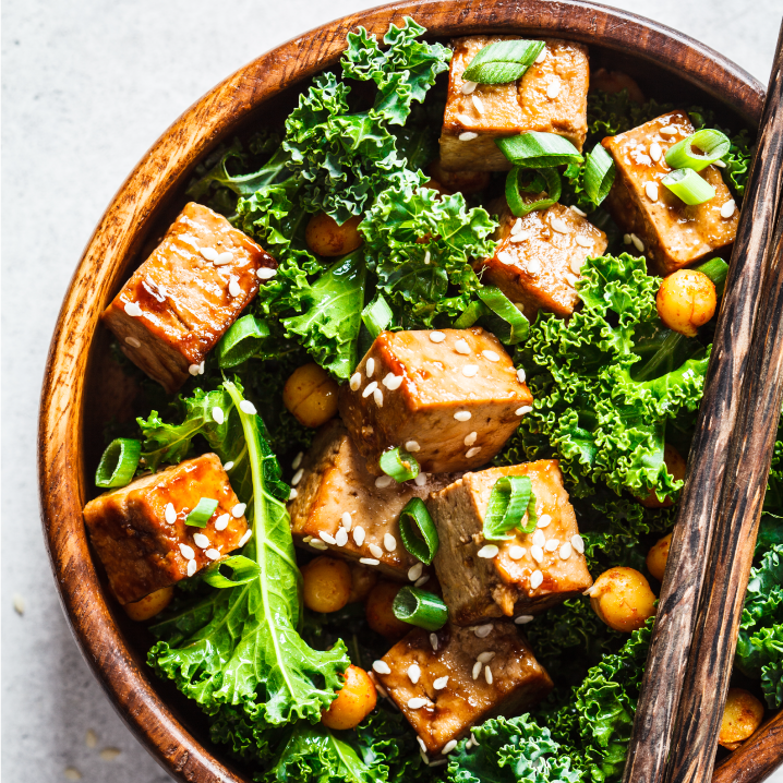 A wooden bowl filled with a meal of fried tofu, kale, and chickpeas