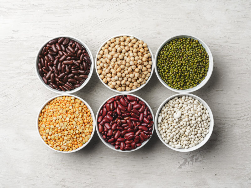 An assortment of beans in bowls on a white table, representing ingredients for plant-based meat