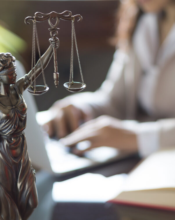 A small figurine of the scales of justice in front of a woman working on her laptop