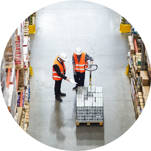 Two workers discuss packed goods pushing a pallet inside a warehouse