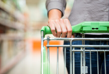 Closeup up of shopper's hand on the handle of a grocery store cart