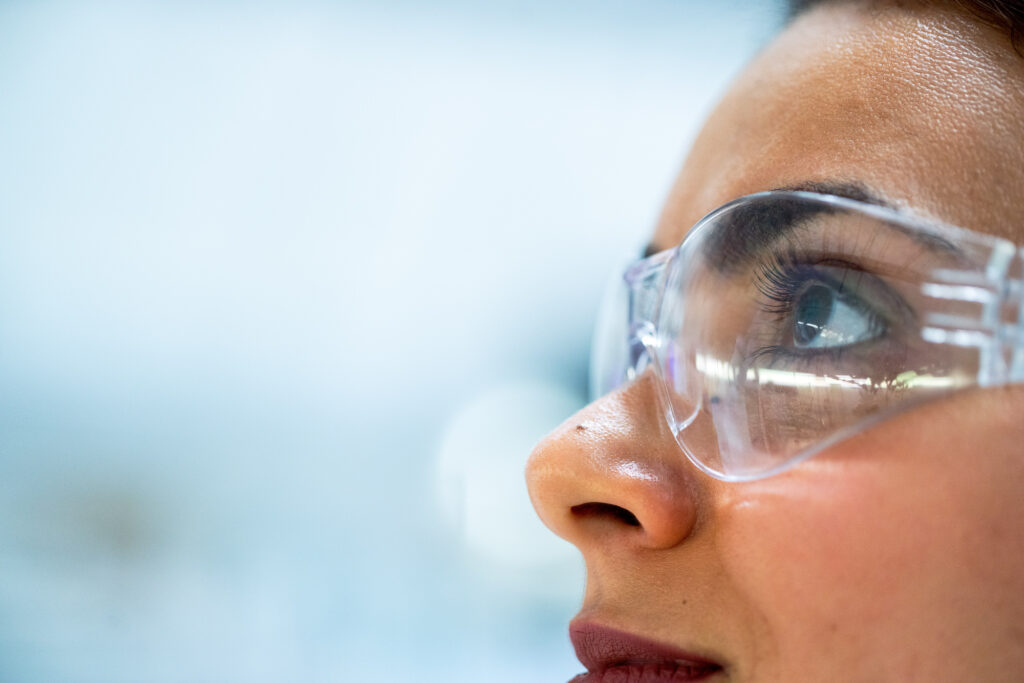 A close up of a female scientist wearing protective clear goggles looking up