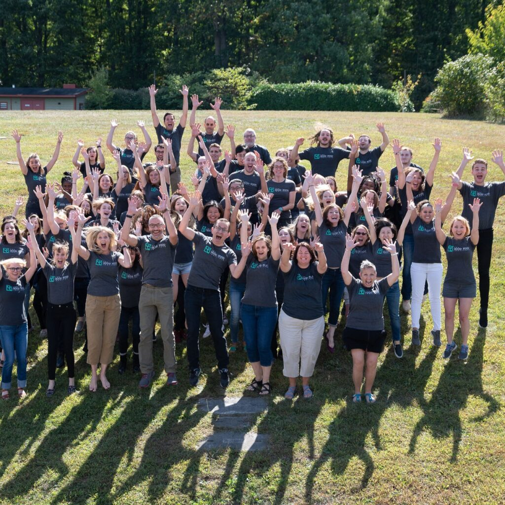 A group of gfi staff jumping with their arms in the air smiling and laughing