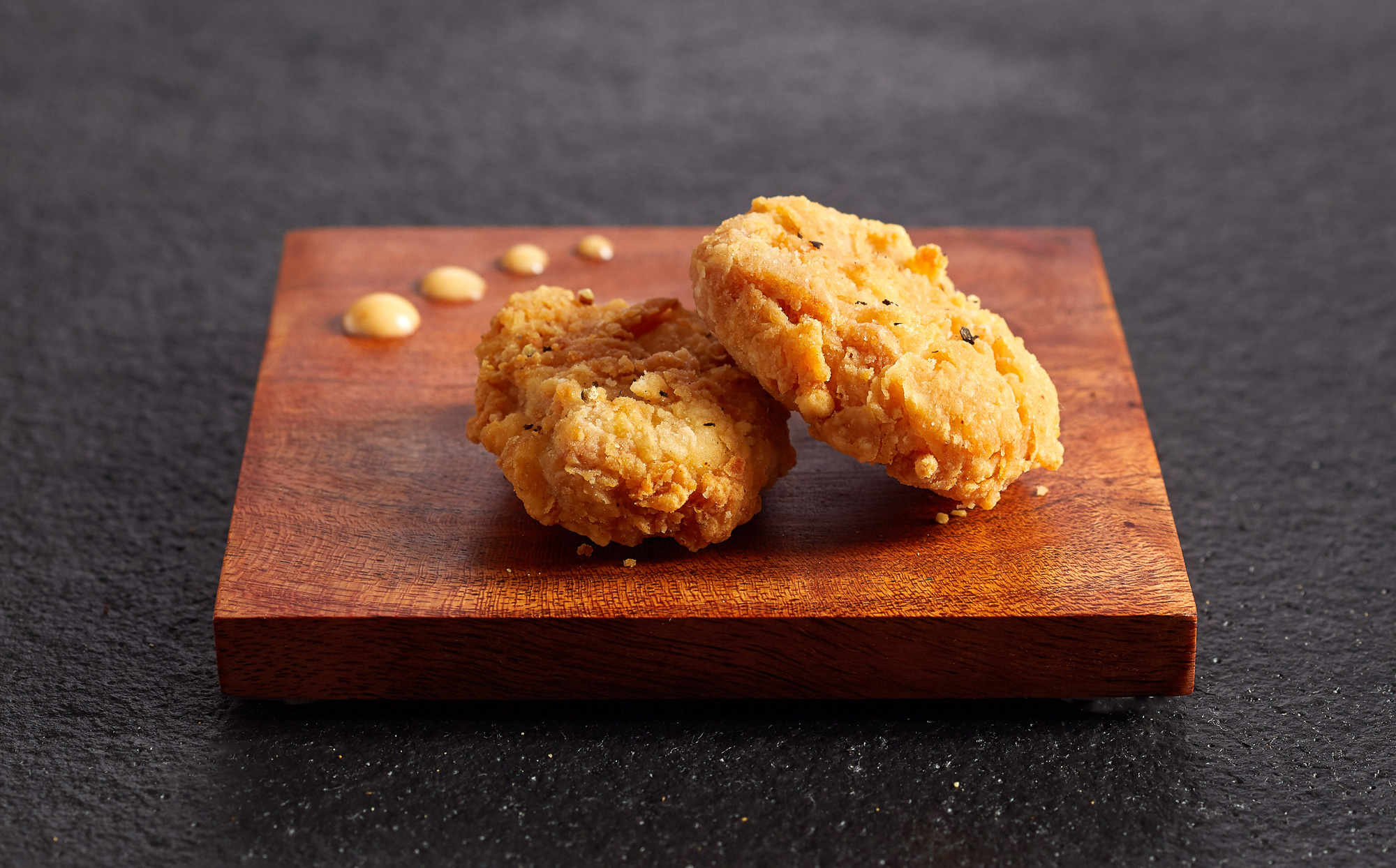 Cultivated chicken on a wood serving dish