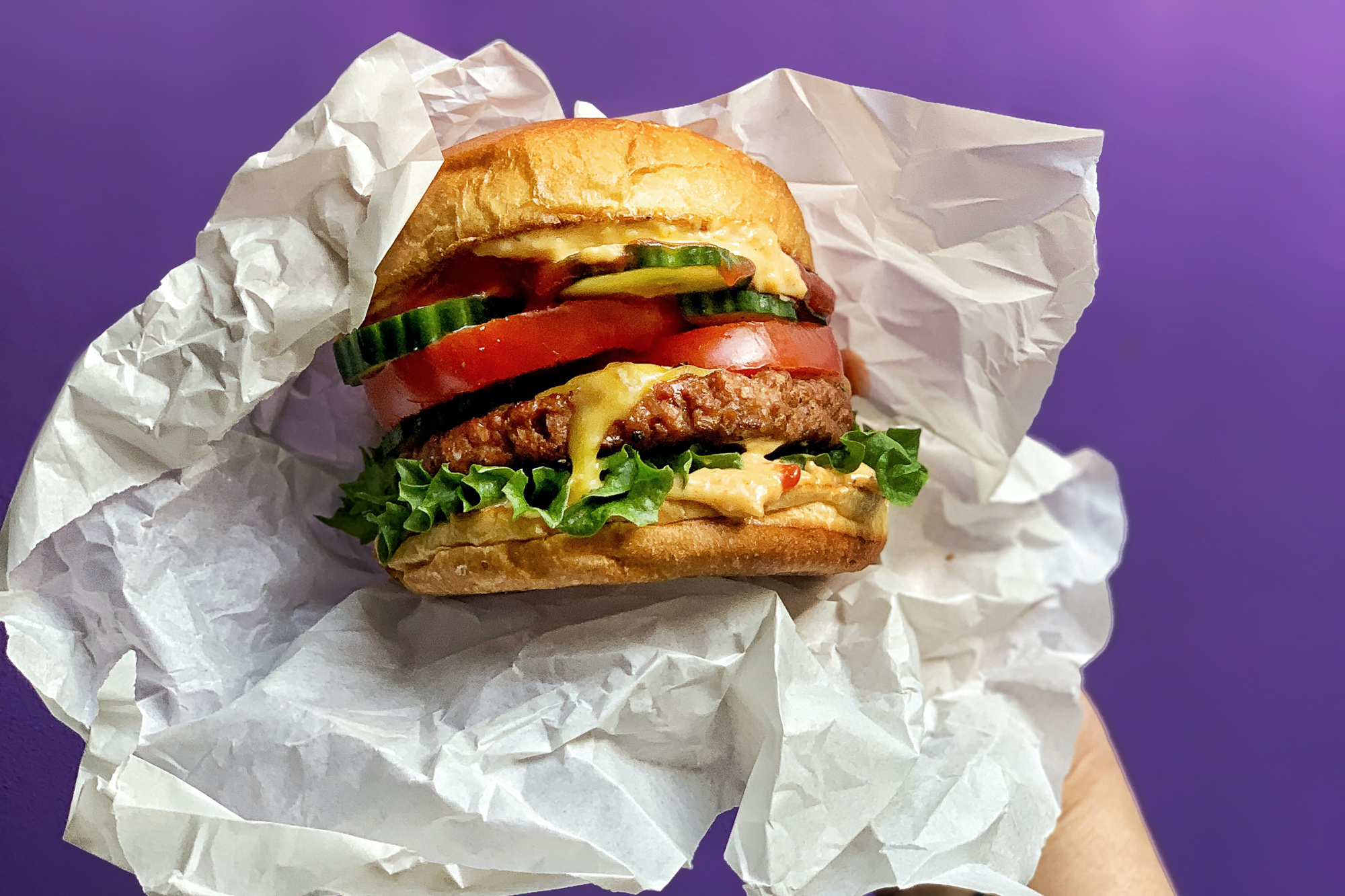 LikeMeat burger in white paper being held in front of a purple background