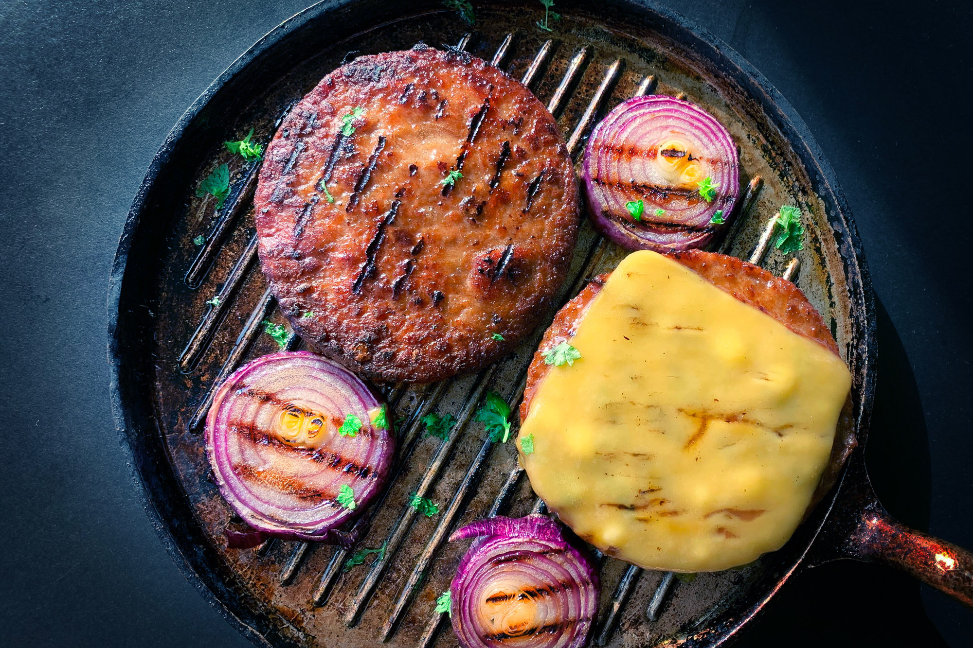 Plant based meat cooking in a cast iron grill
