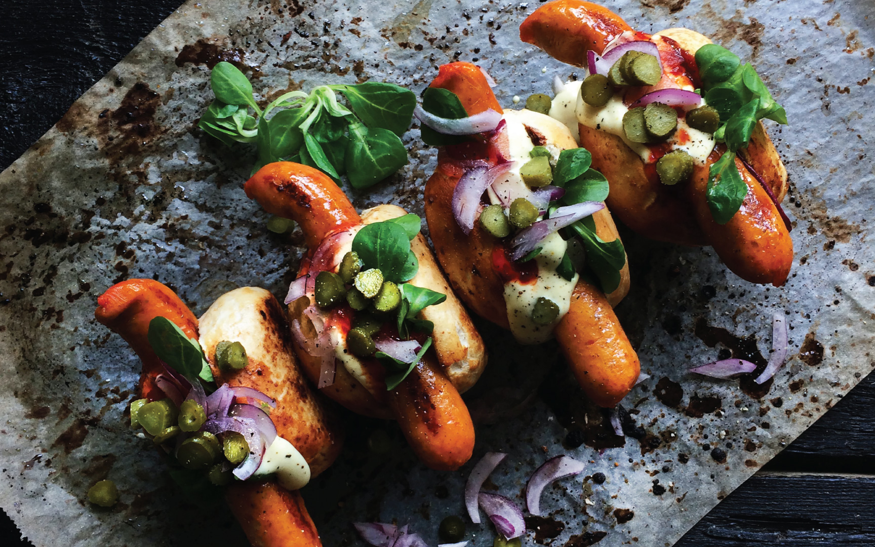Plant-based hot dogs in buns with onions and pickles